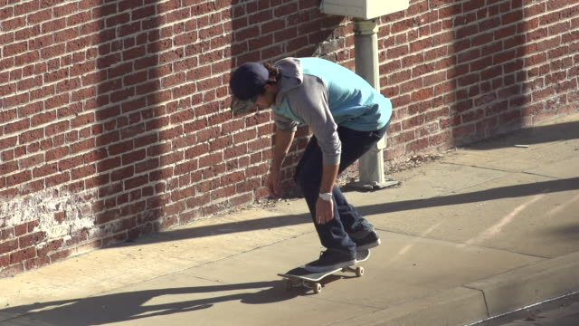 a young man skateboarding on the sidewalk.  - slow motion - filmed at 240 fps - goodsportvideo stock videos and b-roll footage