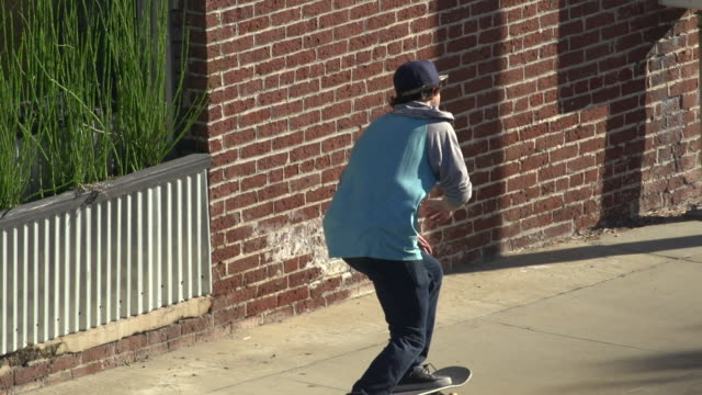 a young man skateboarding on the sidewalk.  - slow motion - goodsportvideo stock videos and b-roll footage