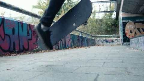 vidéos et rushes de mme young man skateboard, faire des cascades à urbain skate park - a la mode