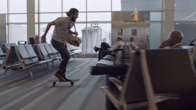 SLO MO. Young man skateboards quickly through airport waiting area in a rush.