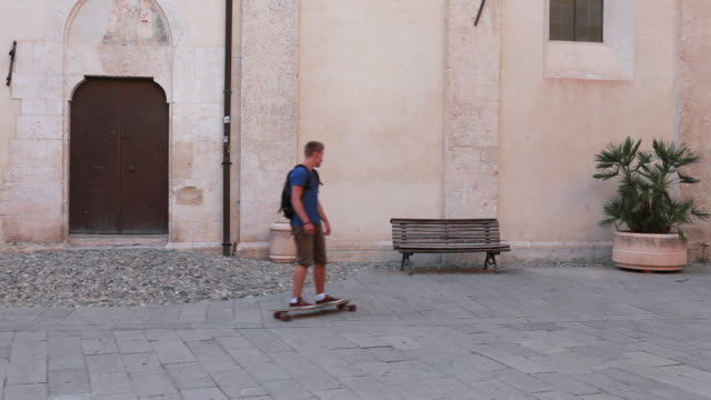 young man skateboards to bench in piazza - skateboard stock videos and b-roll footage