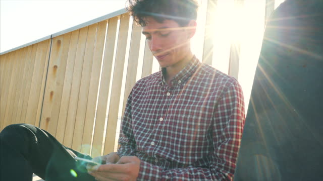 junger mann skater mit seinem smartphone. - sitzen stock-videos und b-roll-filmmaterial