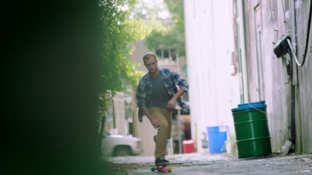 Young man skates through downtown alley on longboard