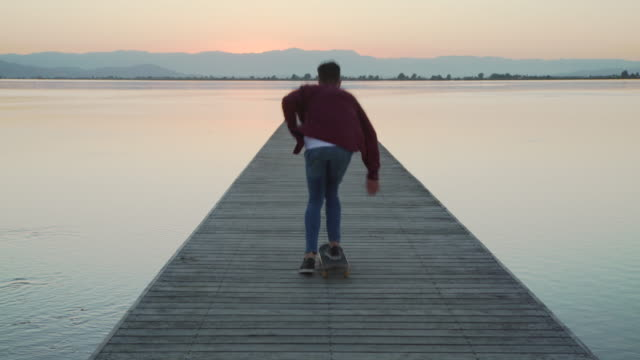 young man skating and feeling free. at the edge of a wooden jetty, cheerful, takes arms up enjoying of the landscape. - plaid shirt stock videos & royalty-free footage