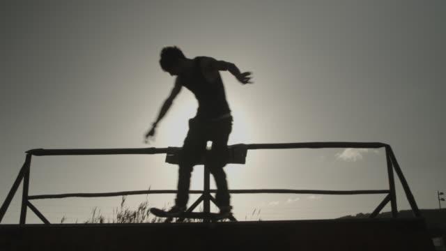 vídeos de stock, filmes e b-roll de young man skating on half pipe in the sun in portugal - parélio