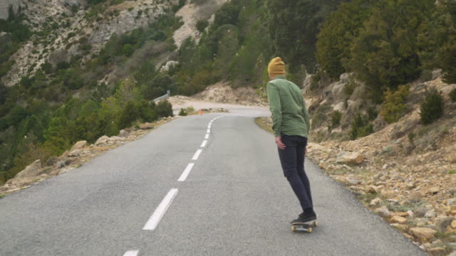 young man skating through a mountain road - one young man only stock videos & royalty-free footage