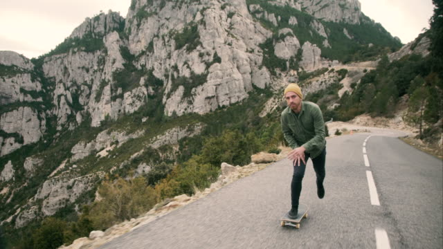 vídeos de stock e filmes b-roll de young man skating through a mountain road - 25 29 anos