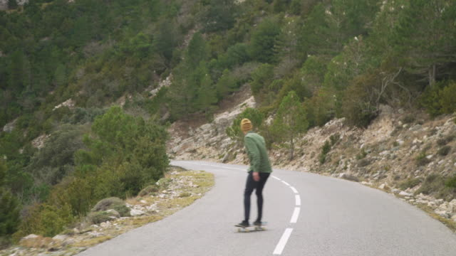 Young man skating through a mountain road