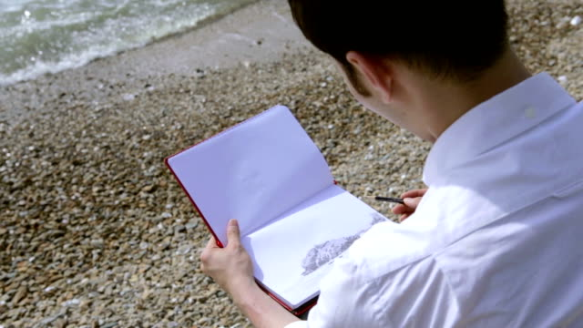 Young man sketching seascape at beach