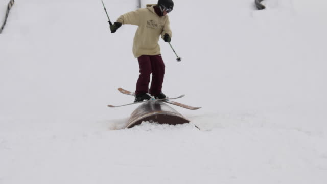 A young man skier performing grind tricks in terrain park.