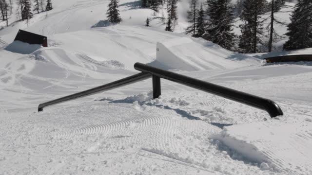 vídeos de stock e filmes b-roll de a young man skier performing grind tricks in terrain park. - bastão de esqui