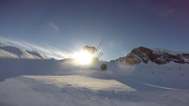 Young man skiing and doing tricks in terrain park on snow covered mountain. - filmed in Kaprun, Austria, Europe