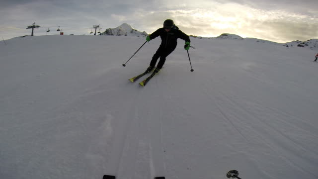 young man skiing down a snow covered mountain. - slow motion - filmed in kaprun, austria, europe - solo uomini giovani video stock e b–roll