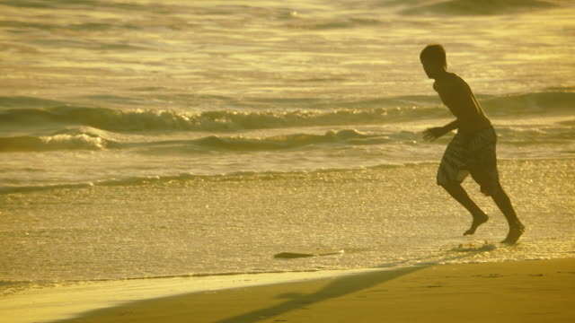 a young man skimboarding in the surf, slow-motion at sunset. - skimboarding stock videos & royalty-free footage