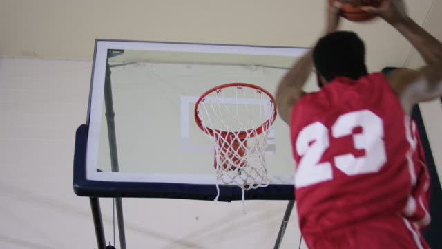 Young man slam dunking a basketball