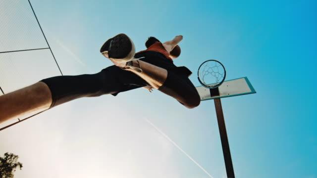 vidéos et rushes de ms super slo mo timewarp effect jeune homme slam dunking basket-ball dans le panier de basket-ball - joueur de basket ball