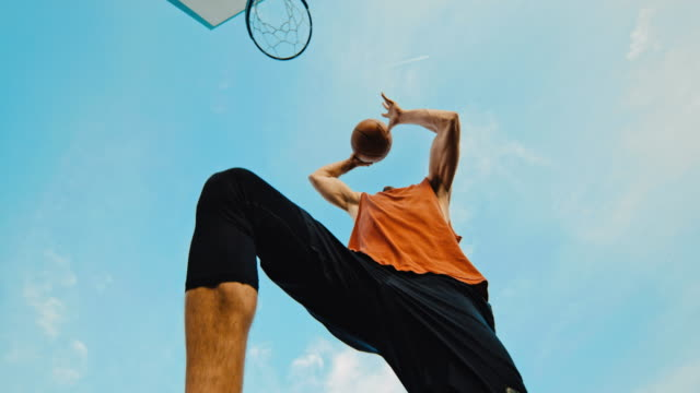 ms super slow motion young man slam dunking basketball - shooting baskets stock videos & royalty-free footage