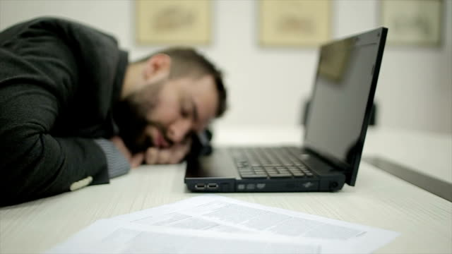 young man sleeping in the office,dolly shoot - snoring stock videos and b-roll footage
