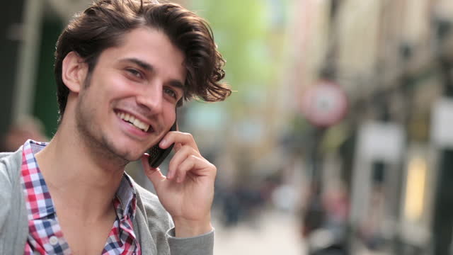 Young man smiles and laughs as he talks in the phone on city street corner.