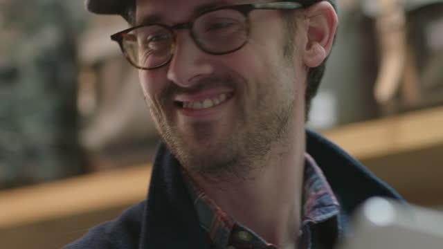 vídeos de stock, filmes e b-roll de cu. young man smiles and signs for purchase on touchscreen at modern shop checkout counter. - balcão de pagamento