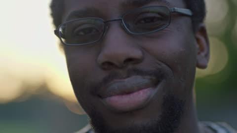 vídeos y material grabado en eventos de stock de cu slo mo. young man smiles at camera. - staring
