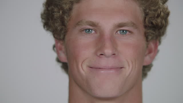 CU SLO MO. Young man smiles into camera.