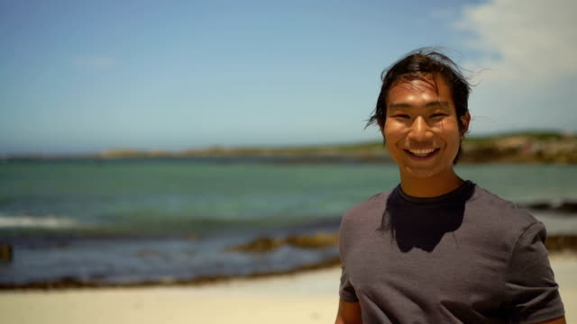 Young man smiling at windy beach