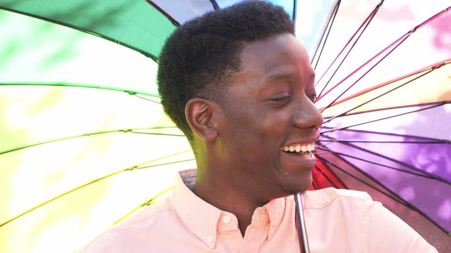 young man smiling holding colourful umbrella - spectrum stock videos & royalty-free footage
