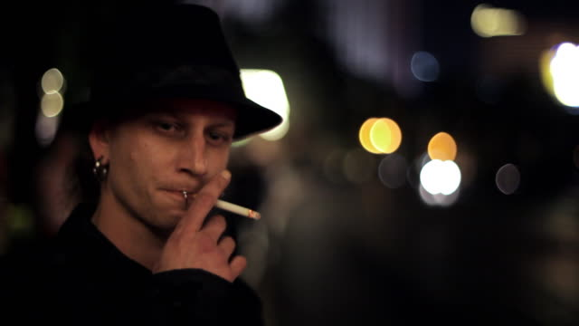 a young man smokes a cigarette on a city street and looks into the camera. - lip ring stock videos and b-roll footage