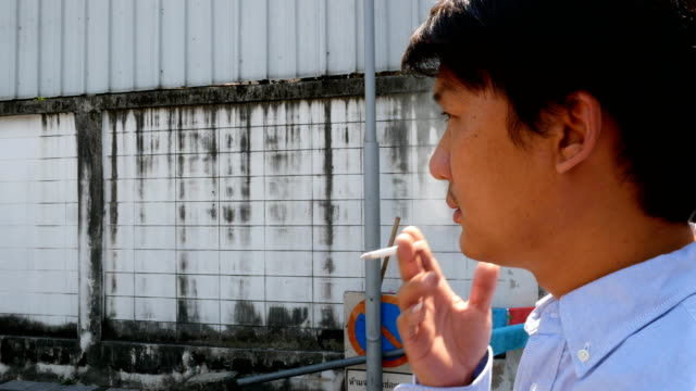 young man smoking cigarette in the city - human settlement stock videos & royalty-free footage