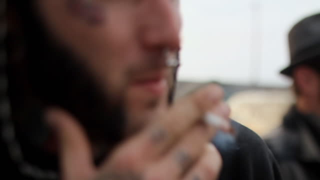 CU Young man smoking cigarette on beach / Jacksonville, Florida, USA