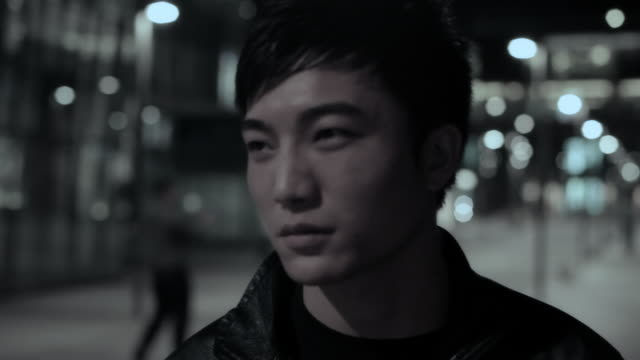 cu young man smoking cigarette on street at night / china - chinese ethnicity stock videos and b-roll footage