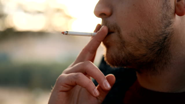 young man smoking cigarette outdoor - smoking issues stock videos & royalty-free footage