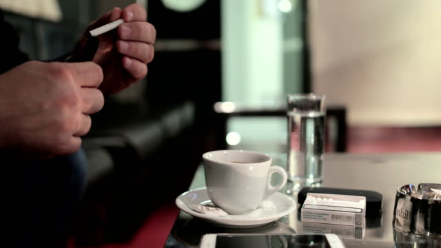Young man smoking e cigarette and drinks coffee