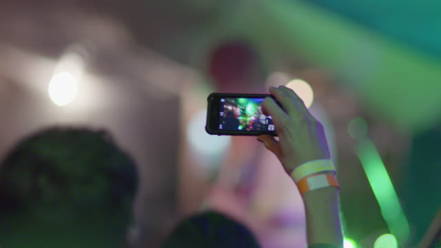 young man snaps photo with smartphone at outdoor rock concert - 可動性点の映像素材/bロール