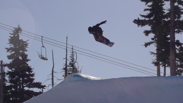 A young man snowboarder going off jumps in a terrain park.  - Super Slow Motion - filmed at 240 fps