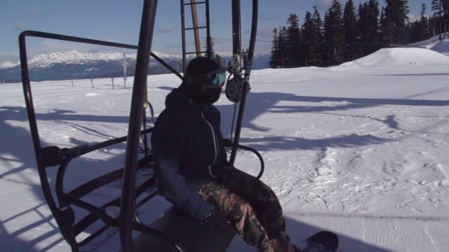 a young man snowboarder riding the chairlift up the mountain. - super slow motion - filmed at 240 fps - goggles sportswear stock videos and b-roll footage