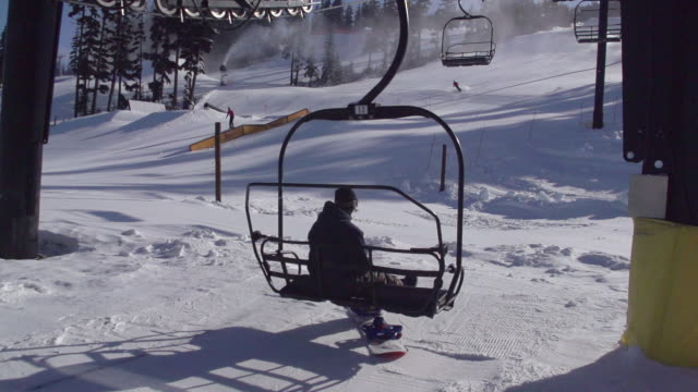 vídeos de stock e filmes b-roll de a young man snowboarder riding the chairlift up the mountain. - pinaceae