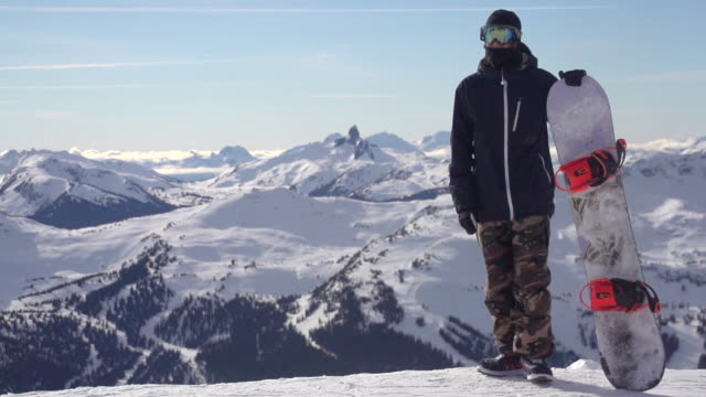 a young man snowboarder standing with his snowboard on a snow covered mountain. - super slow motion - filmed at 240 fps - skibrille stock-videos und b-roll-filmmaterial