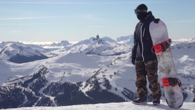 A young man snowboarder standing with his snowboard on a snow covered mountain. - Slow Motion