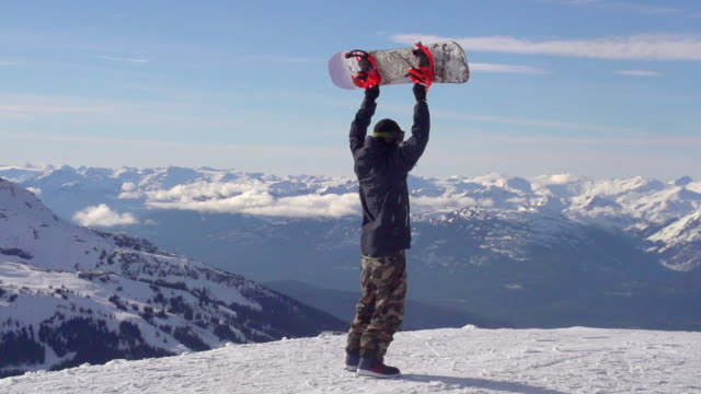 vídeos de stock e filmes b-roll de a young man snowboarder standing with his snowboard over his head on a snow covered mountain. - super slow motion - filmed at 240 fps - roupa de esqui