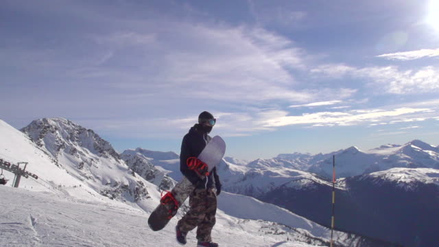 a young man snowboarder walking with his board on a scenic snow covered mountain top. - slow motion - snowboard stock-videos und b-roll-filmmaterial