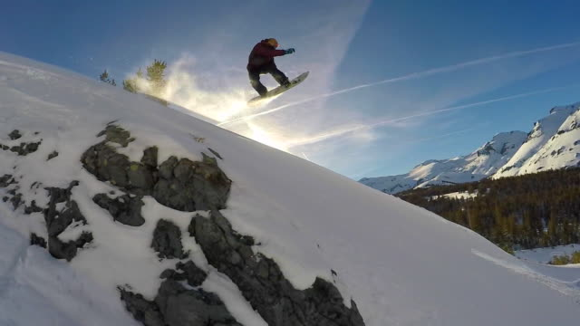 a young man snowboarding and jumping in fresh power snow through trees in the mountains. - snowboard video stock e b–roll
