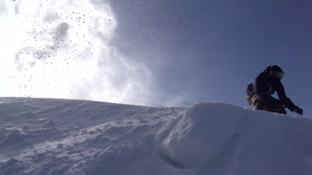 vídeos de stock e filmes b-roll de a young man snowboarding down a snow covered mountain. - super slow motion - filmed at 240 fps - pinaceae