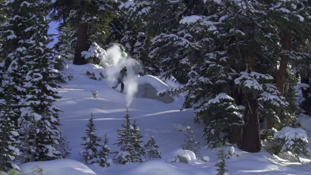a young man snowboarding over rocks and jumps in the mountains. - slow motion - pulverschnee stock-videos und b-roll-filmmaterial