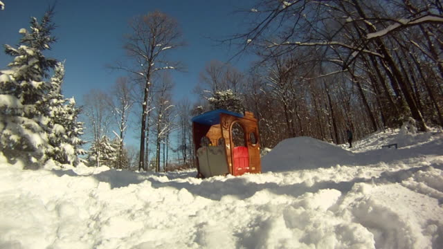 a young man snowboarding through trees and jumping over a playhouse. - model released - hd - spielzeughaus stock-videos und b-roll-filmmaterial