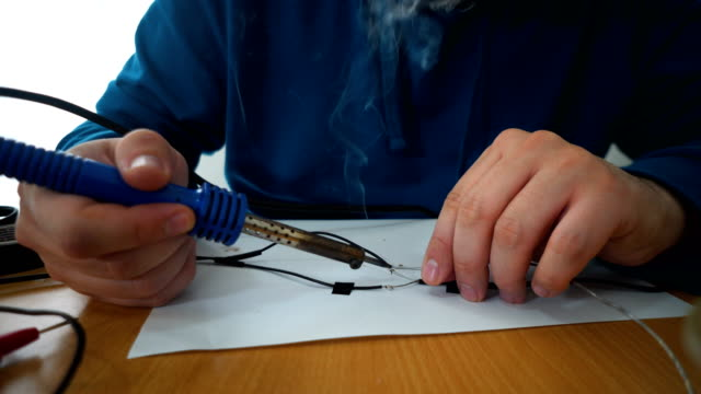 stockvideo's en b-roll-footage met jongeman solderen een solderen draden samen werken aan de tabel. - electrician