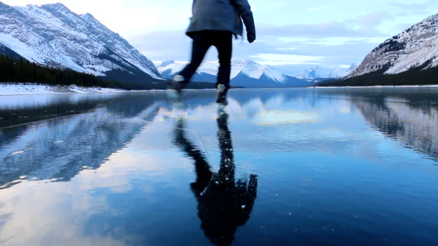 young man solo skates on beautiful mountain lake - ice skating stock videos and b-roll footage