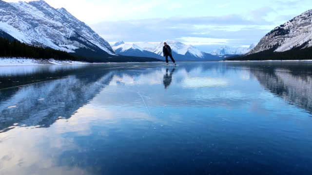 Young man solo skates on beautiful mountain lake