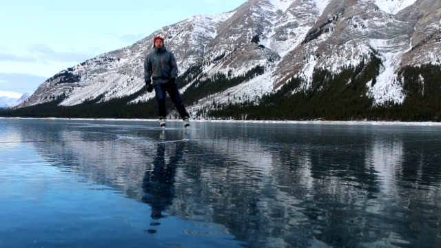 young man solo skates on beautiful mountain lake - frozen video stock e b–roll